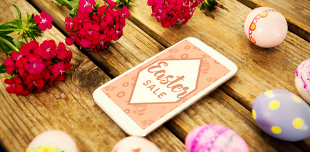 smartphone amidst painted easter eggs and flowers on wooden table Stock Photo