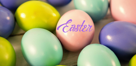 up code: Easter greeting against multicolored easter eggs on wooden surface Stock Photo