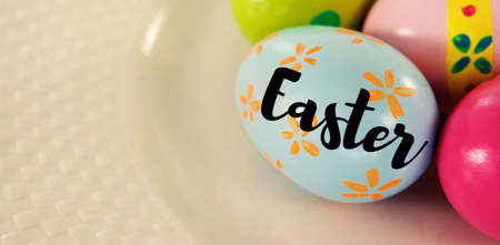 up code: Easter greeting against painted easter eggs on plate