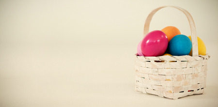 up code: Various Easter eggs in wicker basket on white background Stock Photo