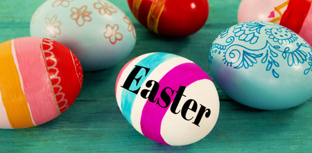 Easter greeting against various easter eggs on wooden surface Stock Photo