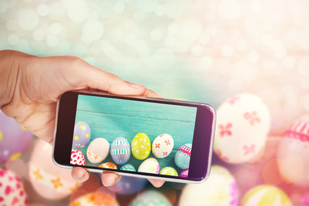 Hand holding mobile phone against white background against painted easter eggs on wooden surface Stock Photo