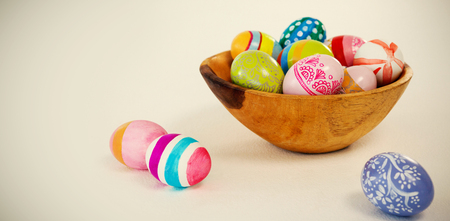 up code: Colorful Easter eggs in wooden bowl on white background
