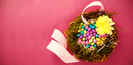 up code: Colorful easter eggs in wicker basket with flower on pink background