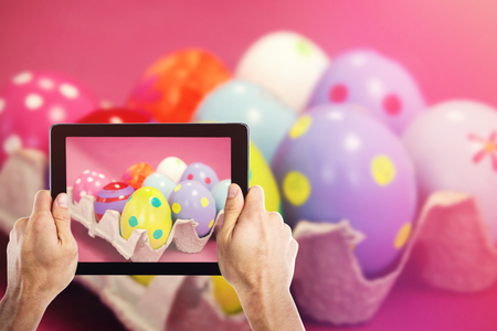 Cropped hand holding digital tablet against colorful easter eggs in egg carton