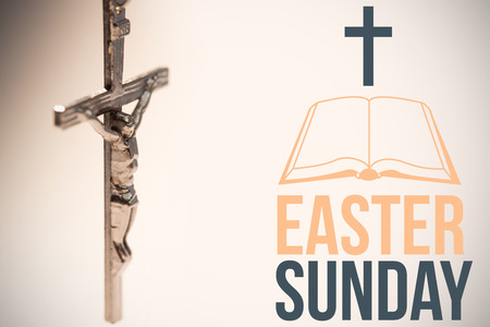easter sunday logo against close up of silver crucifix Stock Photo