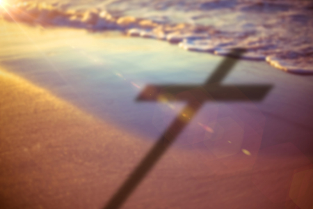 Close up of 3d wooden cross against shore at beach during sunset