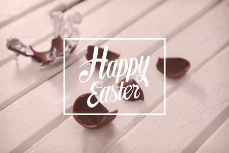indulgence: Happy easter against broken chocolate easter on wooden surface