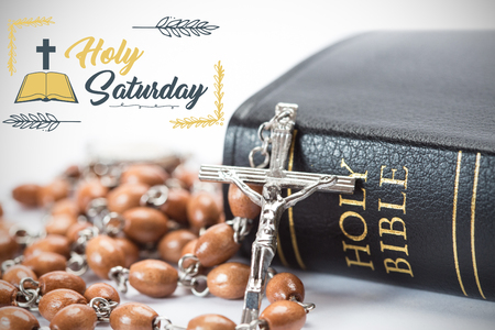Easter message against black leather bound holy bible with rosary beads Stock Photo