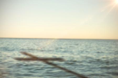 Sluit omhoog van 3d houten kruis tegen overzees tegen duidelijke hemel