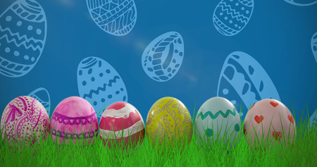 Patterned Easter eggs arranged side by side against royal blue Stock Photo