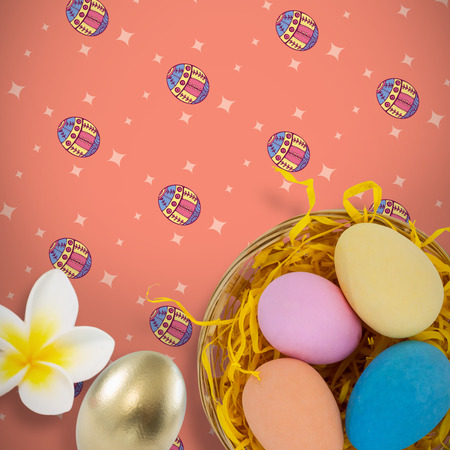 Close-up of frangipani against colorful easter eggs in wicker basket nest