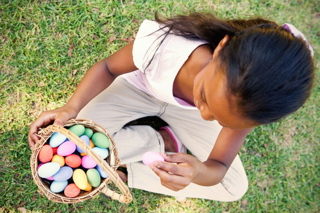 Little girl sitting on grass counting easter eggs on a sunny day