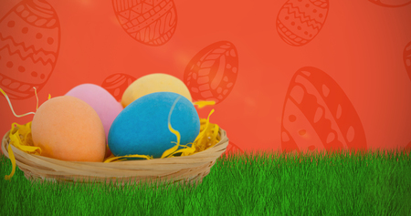 Colorful Easter eggs in wicker basket  against red background Stock Photo
