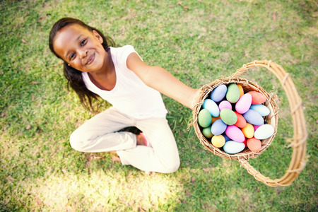 Little girl sitting on grass showing basket of easter eggs to camera on a sunny day