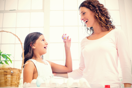 Happy girl showing easter egg to her mother in the living room Stock Photo