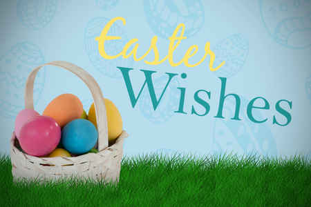Mulit colored Easter eggs in wicker basket against blue background Stock Photo