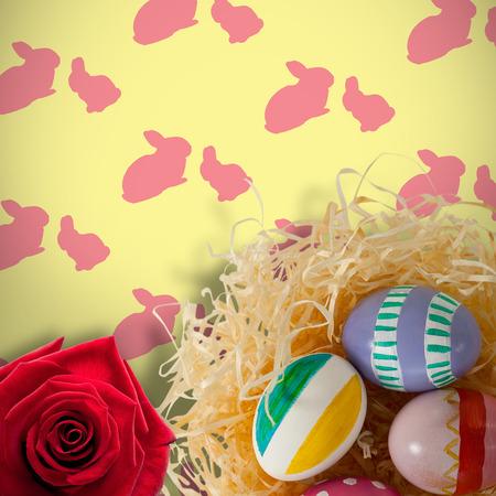 Afbeelding van een roos tegen multi gekleurde paaseieren op papier nest