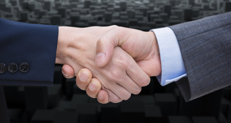 well dressed: Businessman and woman doing handshake against computer graphic image of black blocks Stock Photo