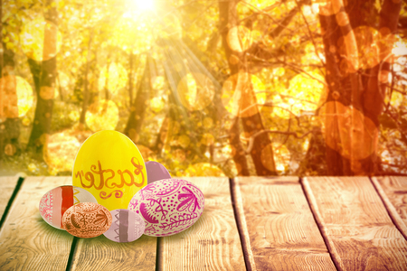 copy text: Multi colored patterned easter eggs against tranquil autumn scene in forest Stock Photo