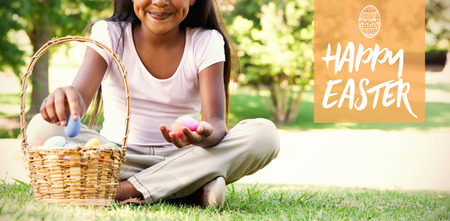 Easter greeting against little girl sitting on grass counting easter eggs smiling at camera Stock Photo