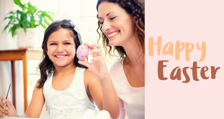 Happy mother and daughter painting easter eggs  against beige background