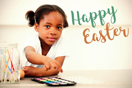 Easter greeting against cute little girl painting eggs in the kitchen Stock Photo
