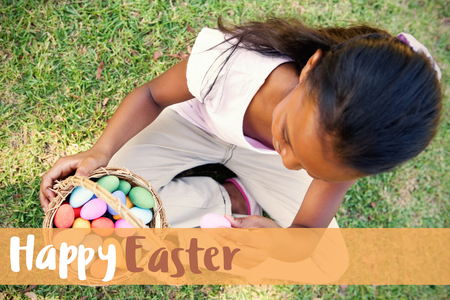 Happy easter against little girl sitting on grass counting easter eggs