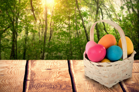 shiny floor: Mulit colored Easter eggs in wicker basket against green forest