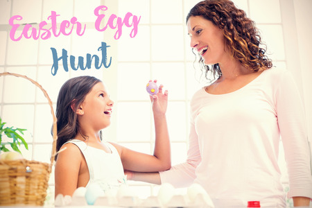 Happy girl showing easter egg to her mother  against easter greeting