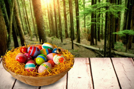 Multi colored easter eggs in wicker basket against tall trees growing in forest Banco de Imagens