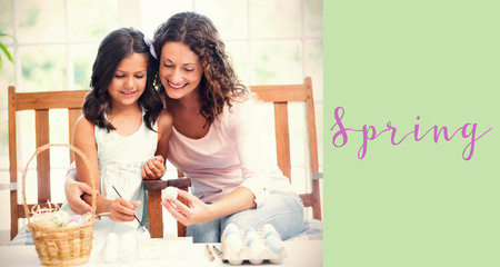 Happy mother and daughter painting easter eggs  against green background