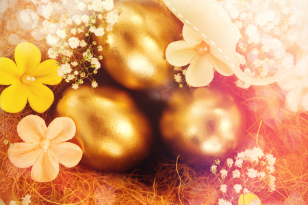 Golden easter eggs with flowers in nest against white background
