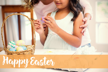 Happy mother and daughter painting easter eggs  against happy easter