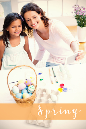 Happy mother and daughter taking selfie against easter greeting Stock Photo
