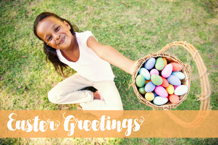 Easter greeting against little girl sitting on grass showing basket of easter eggs to camera