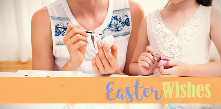 Mother and daughter painting easter eggs against easter greeting