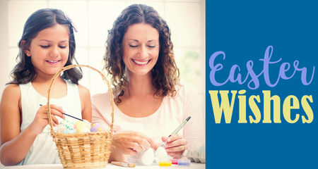 Happy mother and daughter painting easter eggs  against royal blue