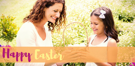 Happy mother and daughter collecting easter eggs against easter greeting Stock Photo