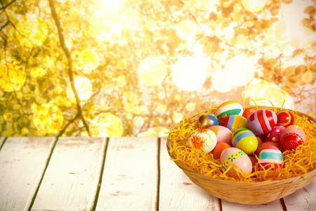 shiny floor: Multi colored easter eggs in wicker basket against tranquil autumn scene in forest