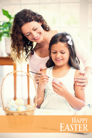 Happy mother and daughter painting easter eggs  against easter greeting Stock Photo