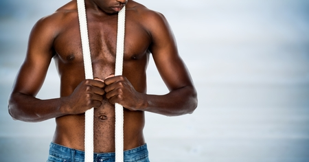 masculinity: Digital composite of Man mid section with rope against blurry blue wood panel