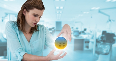 Digital composite of Woman sitting with emoji and flare between hands against blurry blue office Stock Photo