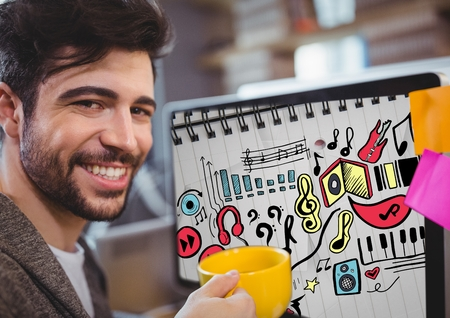Digital composite of Man with mug sitting at computer showing music doodles on sketchbook Stock Photo