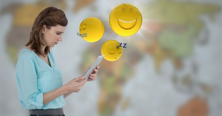 Digital composite of Woman with tablet and emojis with flare against blurry map Stock Photo