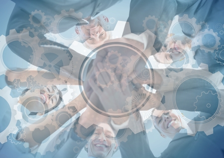 Digital composite of Business team putting hands together with gear graphic overlay Stock Photo