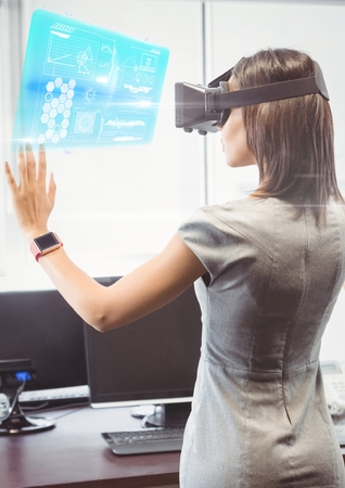 Digital composite of Woman in office wearing VR Virtual Reality Headset with Interface