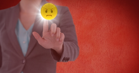 wrath: Digital composite of Business woman mid section touching emoji with flare against red wall Stock Photo