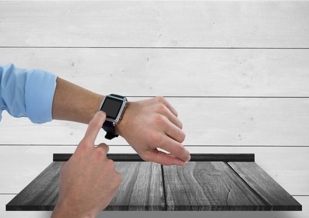 cropped: Digital composite of Arms with smart watch against wood