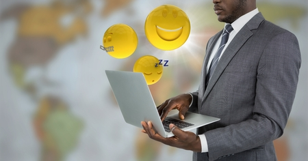 Digital composite of Business man with laptop and emojis with flare against blurry map Stock Photo